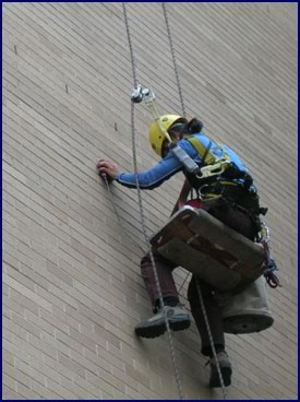 Shan Wo using a pachometer and rope access to locate veneer ties on a high rise elder care facility in Boulder, Colo.