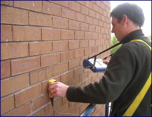 Peter Champe using a pachometer to locate embedded veneer ties.