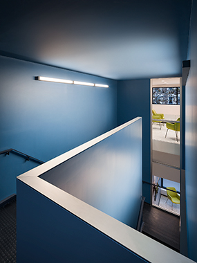 Distinct geometric volumes interact with each other at the reception desk and a new boldly colored enclosed stair volume provides a dramatic transition between floors.