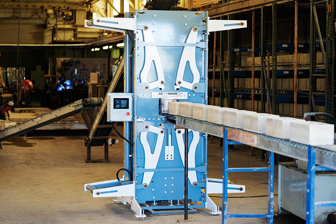 Watershed Materials' high compression masonry block machine produces low cement alternatives to traditional concrete masonry units (CMUs) from unwashed aggregates diverted from quarries or from onsite excavation material diverted from real estate development projects. The machine is shown here at Watershed Materials' pilot block factory and research lab in Napa, Calif.
