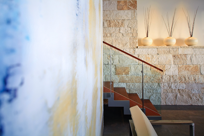 Rough and sleek work together with this textured wall of Chop Face limestone and the smoothness of the steel, glass, and teak stairs.