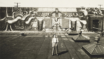 Roberto Berdecio, a close associate of Siqueiros during the 1930s, stands in front of América Tropical mural at the Italian American Museum of Los Angeles. © 2012 Artists Rights Society (ARS), New York/SOMAAP, Mexico City. Photo: The Getty Research Institute