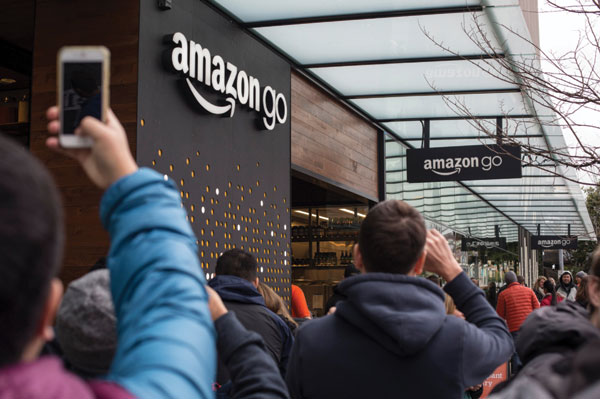 "Shoppers and passers-by get a glimpse of the exterior of one of Amazon's ""brick and mortar"" stores in Seattle in December 2016. (Photo by David Ryder for The New York Times.)"