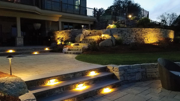 The combination of lighting with masonry extends the hours that homeowners can enjoy their outdoor living area. This home in Massachusetts now has lights installed on the steps, in the pavers and in the stone walls.