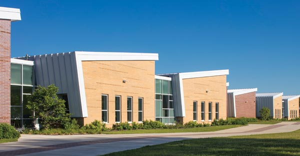 Light and dark brick alternates between classroom wings on the east side of the CCSD59 ELC. The thinner brick, different textures, and horizontal bands of color break down the scale and create a playful appearance. Photo © AJ Brown Imaging