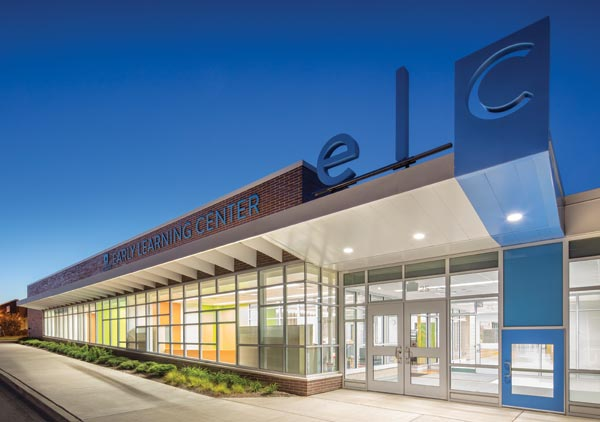 The child-sized blue door at the CCSD59 ELC entry gives students a comforting first impression — this facility is designed for them. Brick above and below the glazing complements the adjacent middle school. Photo © AJ Brown Imaging